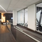 A multifaceted facade behind the reception desk of floor, flooring, glass, interior design, office, window, gray