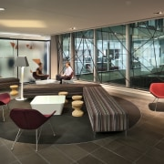 A multifaceted facade behind the reception desk of architecture, floor, flooring, furniture, interior design, living room, lobby, table, black