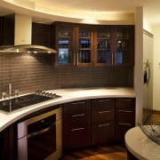 The graceful curves of this kitchen are picked cabinetry, countertop, flooring, interior design, kitchen, lighting, room, brown, black