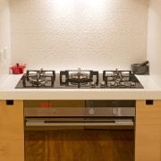 Toni Roberts kitchen with Fisher & Paykel appliances. cabinetry, countertop, floor, flooring, hardwood, interior design, kitchen, kitchen stove, room, under cabinet lighting, orange, brown, white