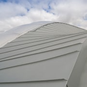The roof was chosen in part for its angle, architecture, building, cloud, daylighting, daytime, line, roof, sky, gray