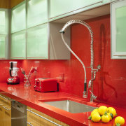 Fixtures and fittings in this text kitchen are cabinetry, ceiling, countertop, interior design, kitchen, orange, room, under cabinet lighting, red