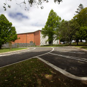 The building framework, protruding stage and attached canopy architecture, area, asphalt, campus, estate, grass, house, landscape, park, plant, property, real estate, recreation, residential area, road surface, sky, structure, suburb, tree, brown, black