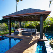 In this landscape design, the wide-plank timber decking arecales, leisure, outdoor structure, palm tree, property, real estate, resort, swimming pool, vacation, water