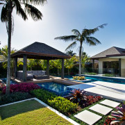 In this tropical-themed pool environment, sandstone paving and arecales, estate, home, house, leisure, palm tree, plant, property, real estate, resort, swimming pool, tree, villa