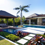 The architecture of this house is enhanced by backyard, cottage, estate, home, house, landscaping, leisure, palm tree, property, real estate, residential area, resort, swimming pool, villa, white