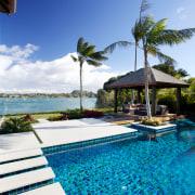 Multi-hued tiles capture the sense of the ocean arecales, caribbean, condominium, estate, leisure, palm tree, property, real estate, reflection, resort, resort town, sea, sky, swimming pool, tree, tropics, vacation, villa, water, blue, teal