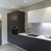 Geometric forms define this new kitchen designed by cabinetry, countertop, interior design, kitchen, real estate, room, gray, black