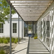 A steel and wood trellis on this pergola architecture, courtyard, home, house, porch, real estate, walkway, white, brown, gray