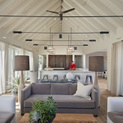 With its soaring ceiling, and exposed rafters and ceiling, daylighting, estate, home, house, interior design, living room, porch, real estate, window, gray