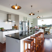 The island features a single slab of pure countertop, hardwood, home, interior design, kitchen, real estate, room, gray