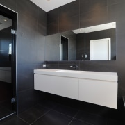 Monochromatic and dramatic, this bathroom is brought together architecture, bathroom, floor, interior design, property, real estate, room, tile, black, gray
