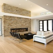 the natural stone wall appears to slice through ceiling, floor, flooring, hardwood, interior design, laminate flooring, living room, real estate, room, wall, wood, wood flooring, white