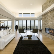 the natural stone wall appears to slice through ceiling, floor, flooring, interior design, living room, property, real estate, room, gray