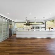 Sleek contemporary kitchen with Smeg appliances - Sleek countertop, floor, flooring, hardwood, house, interior design, kitchen, laminate flooring, real estate, wood flooring, white