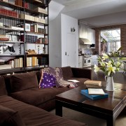 Stairs wind up behind the bookcase in this furniture, home, interior design, living room, room, gray