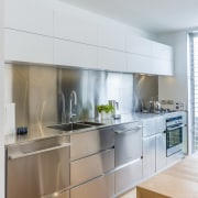 Brushed stainless steel features on the cabinets, benchtop cabinetry, countertop, cuisine classique, interior design, kitchen, room, under cabinet lighting, gray, white