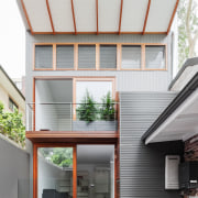 The two-storey section of this home echoes the architecture, building, daylighting, elevation, facade, home, house, real estate, residential area, roof, siding, window, white