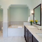 The toilet has its own alcove with an bathroom, bathroom accessory, floor, home, interior design, room, sink, tile, gray