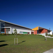 Hobsonville Point Primary and Secondary Schools provide enquiry-based architecture, corporate headquarters, facade, grass, home, house, property, real estate, residential area, sky, blue, brown