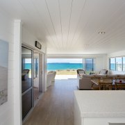 This beachfront holiday home living room has an apartment, ceiling, daylighting, floor, house, interior design, real estate, room, window, gray