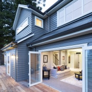 Bifolding doors open up to an expansive deck facade, home, house, real estate, roof, siding, window, teal