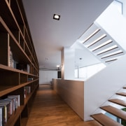 A bookcase on the first floor of this apartment, architecture, ceiling, daylighting, floor, handrail, hardwood, house, interior design, loft, real estate, stairs, wood, white