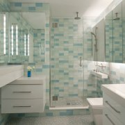 A line of mirrors bounces light around this bathroom, floor, glass, home, interior design, room, tile, gray, green
