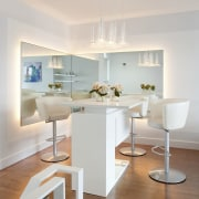 An all-white bar is at one side of ceiling, chair, dining room, floor, furniture, home, interior design, light fixture, living room, product design, room, table, wall, gray