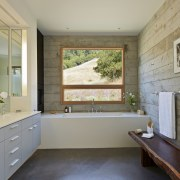 The board-formed concrete gives the walls of this architecture, bathroom, countertop, daylighting, estate, floor, flooring, home, house, interior design, kitchen, real estate, room, window, gray, orange