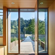 A wood plank walkway over a bridge leads architecture, daylighting, door, estate, home, house, interior design, property, real estate, wall, window, wood