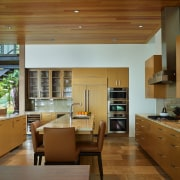The kitchen, at one end of the open-plan architecture, cabinetry, ceiling, countertop, cuisine classique, daylighting, hardwood, house, interior design, kitchen, real estate, wood, brown