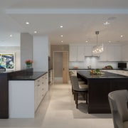 The two islands dictate pedestrian flow into this countertop, interior design, kitchen, real estate, room, gray