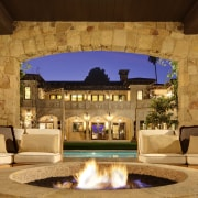While the guest house is different in scale backyard, estate, hacienda, home, interior design, lighting, patio, property, real estate, villa, brown, orange