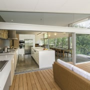This galley-style kitchen extends through to a covered architecture, house, interior design, real estate, white