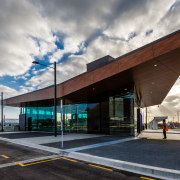 A substantial, timber-clad gullwing roof appears to float architecture, building, cloud, corporate headquarters, facade, infrastructure, sky, gray, black