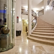 Grand, sweeping marble staircase and floor greets the apartment, estate, floor, flooring, home, interior design, lobby, property, real estate, stairs, gray, orange, brown