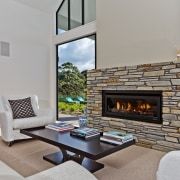 Framed in Central Otago schist, the Escea DL1100 fireplace, hearth, home, interior design, living room, real estate, gray