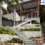 A series of zigzagging stone steps lead up architecture, courtyard, estate, facade, home, house, outdoor structure, real estate, residential area, walkway, gray, brown