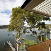 This waterfront house incorporates a renovated boatshed and architecture, cottage, home, house, outdoor structure, plant, real estate, roof, sky, tree, water, wood, brown