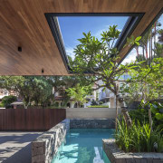 A cutout in the canopy echoes the shape architecture, arecales, backyard, courtyard, estate, home, house, leisure, outdoor structure, palm tree, plant, property, real estate, resort, swimming pool, tree, villa, water, brown