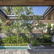 A reflection pool is a feature of the arecales, backyard, courtyard, estate, home, house, outdoor structure, plant, property, real estate, tree, yard, brown