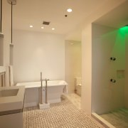 This shower features body sprays as well as bathroom, ceiling, estate, floor, home, interior design, lighting, real estate, room, orange, brown