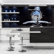 This kitchen incorporates a large backpainted splashback featuring furniture, interior design, product design, white, black