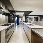 The sandstone benchtop on this island sits atop countertop, interior design, kitchen, gray, black