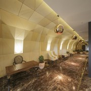 A tessellated motif on the facade can be ceiling, floor, flooring, interior design, lobby, brown, orange