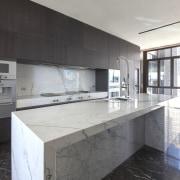 This white marble kitchen island and splashback contrast architecture, countertop, house, interior design, kitchen, property, real estate, white, black
