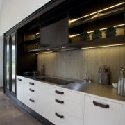 Concrete also forms the splashback for the cooking cabinetry, countertop, cuisine classique, interior design, kitchen, under cabinet lighting, gray, black
