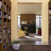 With bookshelves lining both sides, the entry to bookcase, bookselling, furniture, institution, interior design, library, library science, living room, public library, shelf, shelving, orange