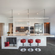 Sleek surfaces, red bar stools and high-tech Bosch countertop, house, interior design, kitchen, real estate, table, gray